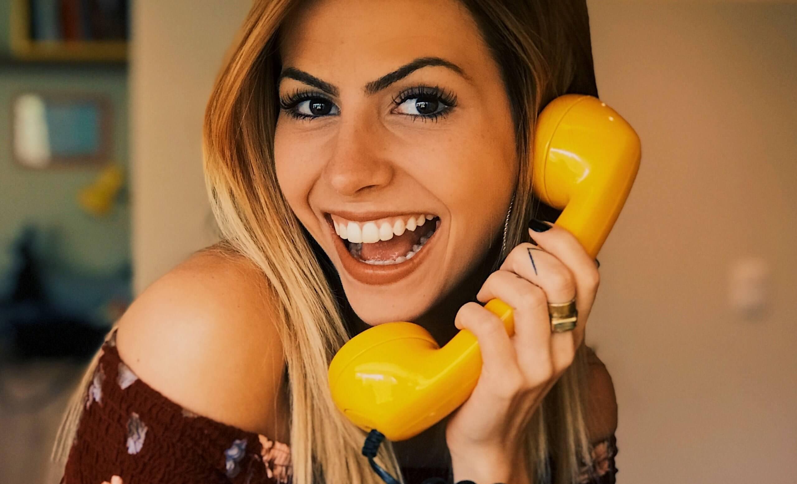 Roześmiana kobieta zżółtą słuchawką telefoniczną