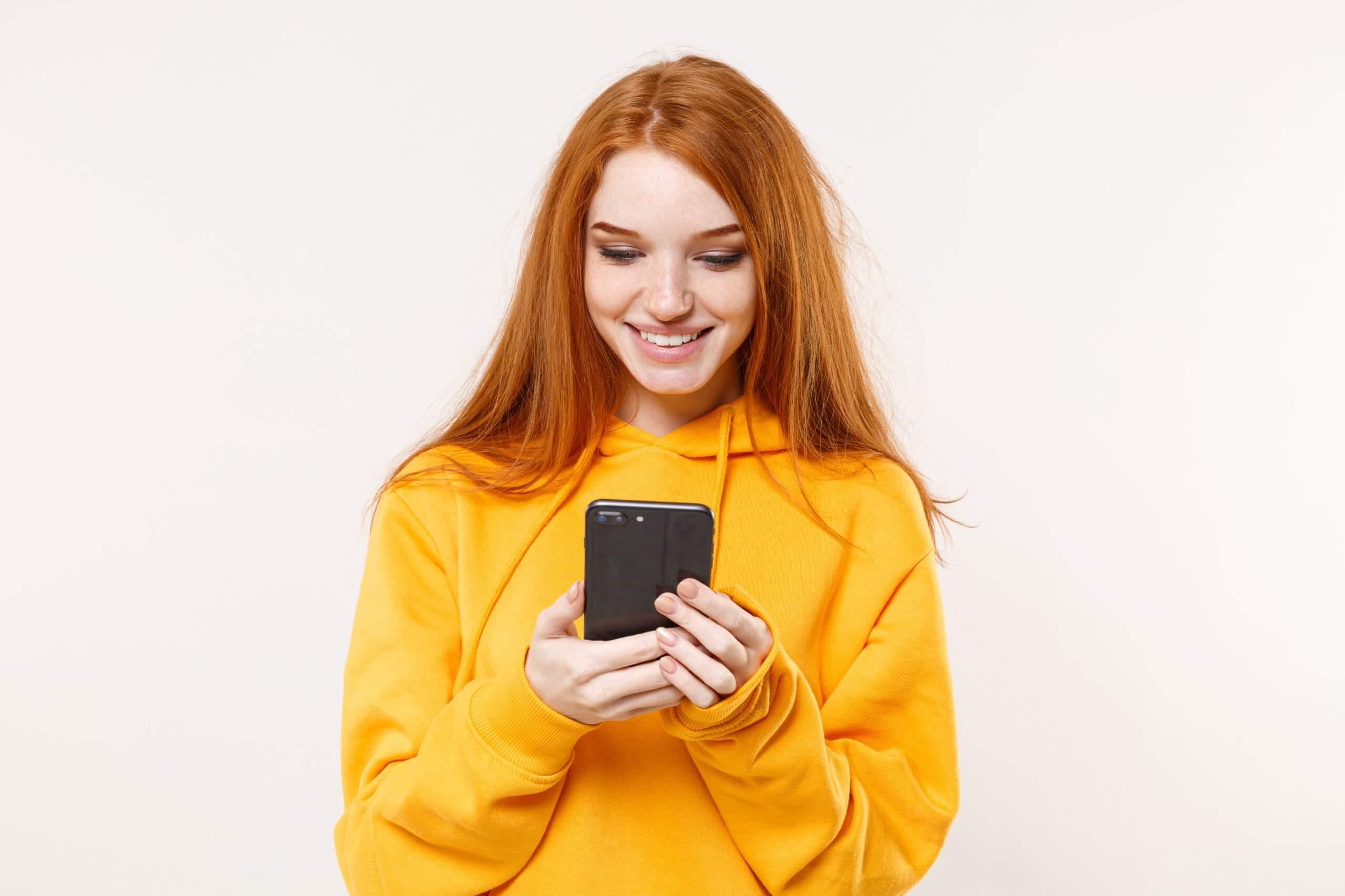 uśmiechnięta ruda kobieta w żółtej bluzie wpatrzona w smartfon